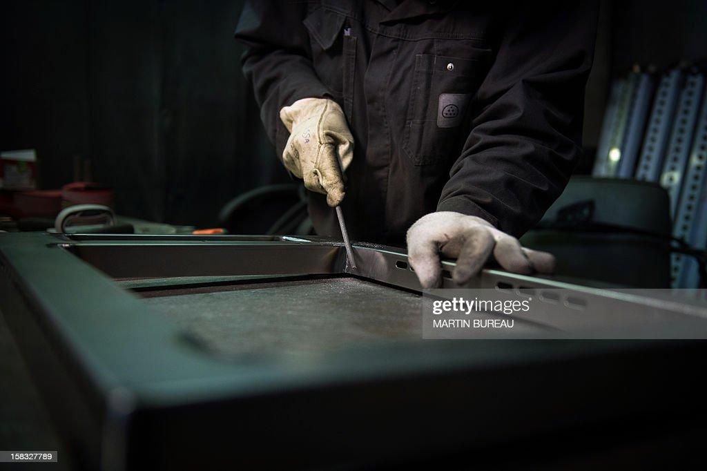 An employee of French cooker maker 'La Cornue' works in the factory on December 13, 2012, in Saint-Ouen-l'Aumone, north of Paris. AFP PHOTO / MARTIN BUREAU
