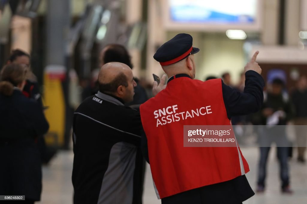 An employee (R) of French state-owned rail operator SNCF helps a passenger at the Gare de Lyon railway station on June 1, 2016 in Paris, at the start of a strike by employees of French state-owned rail operator SNCF to protest against government labour reforms. Rail strikes in France are expected to take full effect, disrupting transport across the country just over a week before the Euro 2016 football championship starts. / AFP / KENZO