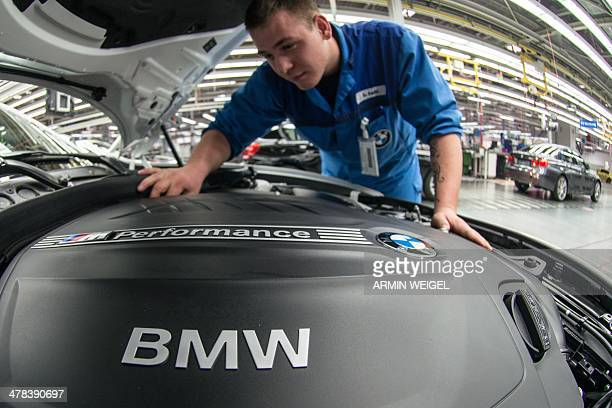 An employee of German car maker BMW works at the company's plant in Regensburg southern Germany on March 13 2014 German topoftherange car maker BMW...