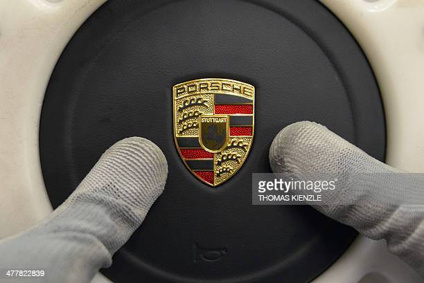An employee of German car producer Porsche fixes the company's logo on the steering wheel of a Porsche 911 sportscar on the production line in the...