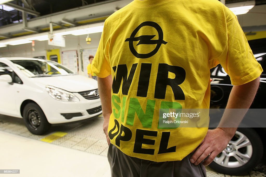 An employee of German carmaker Adam Opel GmbH stands next to an Opel Corsa at a plant on May 4, 2009 in Eisenach, Germany. Representatives of the German government, officials of car manufacturer Opel and managers of Italian carmaker Fiat will meet today in Berlin to discuss a merger between Fiat, Opel and U.S. carmaker Chrysler.