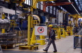 An employee of German industrial giant Siemens walks past the production line at the Gas turbine plant on November 8 2012 in Berlin Siemens launched...