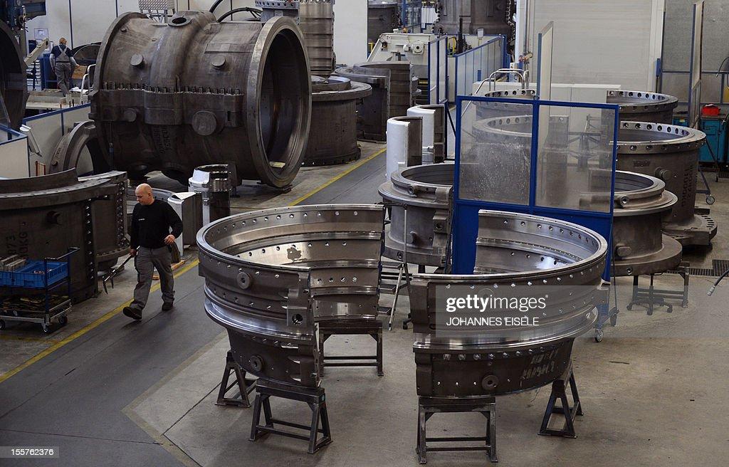 An employee of German industrial giant Siemens works on a housing of a Gas Turbine in the turbine plant on November 8 2012 in Berlin German...