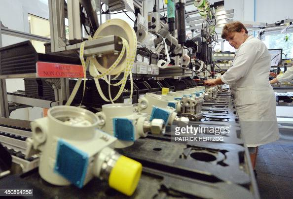 An employee of German multinational group Siemens checks measuring devices on June 19 during a visit of Siemens France president of the Siemens site...