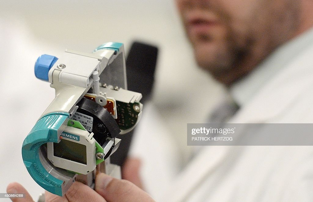 An employee of German multinational group Siemens holds a measuring device on June 19 during a visit of Siemens France president of the Siemens site...
