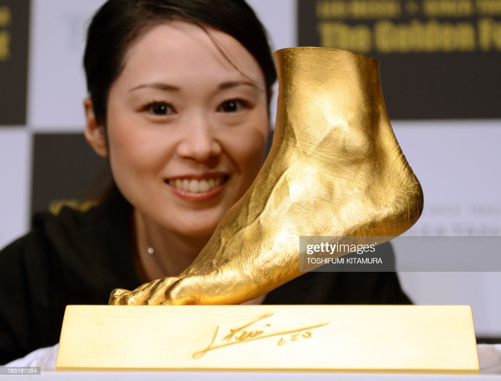 An employee of Ginza Tanaka poses beside the golden replica of football star Lionel Messi of Argentine's left foot during its press preview in Tokyo on March 6, 2013. Priced at about 5.25 million USD, the 25-kilogram golden foot was created by Tokyo-based jewelry retailer, Ginza Tanaka, to commemorate Messi's record-breaking Ballon d'Or for four consecutive years and the world-record 91 goals he scored a calender year.