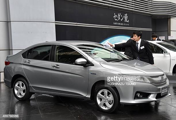 An employee of Japanese auto giant Honda Motor wipes rain off the company's new hybrid sedan 'Grace' after a presentation at the company's...