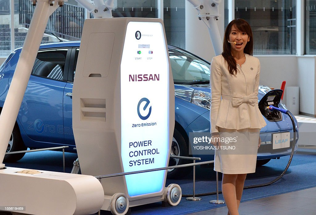 An employee of Japanese auto maker Nissan Motor displays an electric power control system for the company's electric vehicle Leaf (background) at the company's showroom in Yokohama, suburban Tokyo on November 6, 2012. Nissan slashed its full-year forecast by 20 percent due to a strong yen, a slump in Europe and concerns over the impact of a territorial row with China. AFP PHOTO / Yoshikazu TSUNO