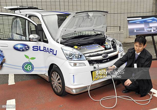 An employee of Japanese automaker Fuji Heavy Industries known as Subaru brand displays the company's electric vehicle 'Stera Plugin' which can charge...