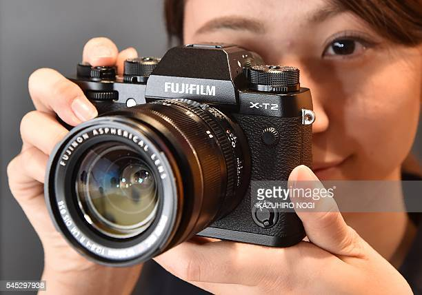 An employee of Japanese camera maker Fujifilm displays the company's new XT2 mirrorless digital camera equipped with advanced autofocus functions and...