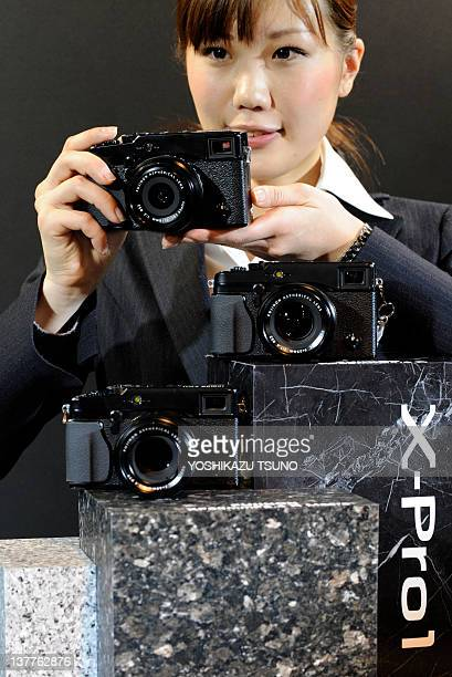 An employee of Japanese camera manufacturer Fujifilm displays the company's new interchangeable lens digital camera 'XPro1' equipped with a 163...