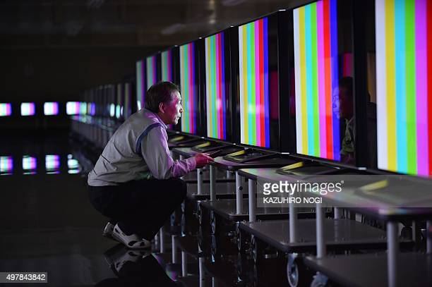 An employee of Japanese electronics giant Sharp performs inspections on AQUOS 4K televisions in a room set at 40 degrees Celsius at the company's...