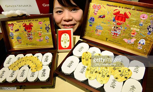 An employee of Japanese jeweler Ginza Tanaka poses next to a box filled with 50 pieces of 30g oval pure gold coins and 10g oval pure gold coins...