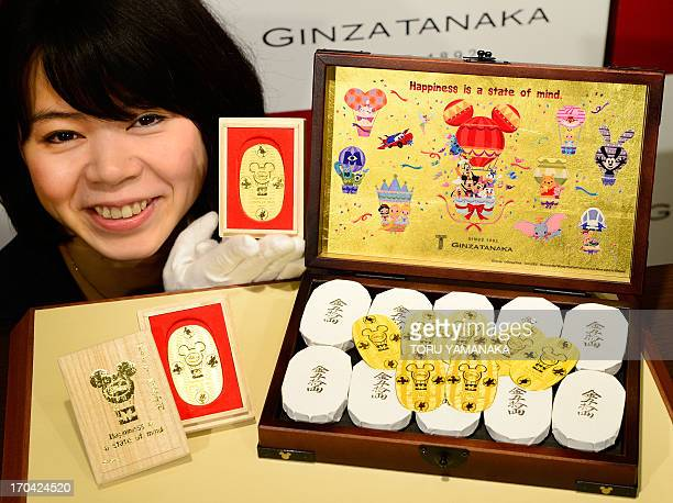 An employee of Japanese jeweler Ginza Tanaka poses next to a box filled with 50 pieces of 30g oval pure gold coins engraved with Walt Disney and...