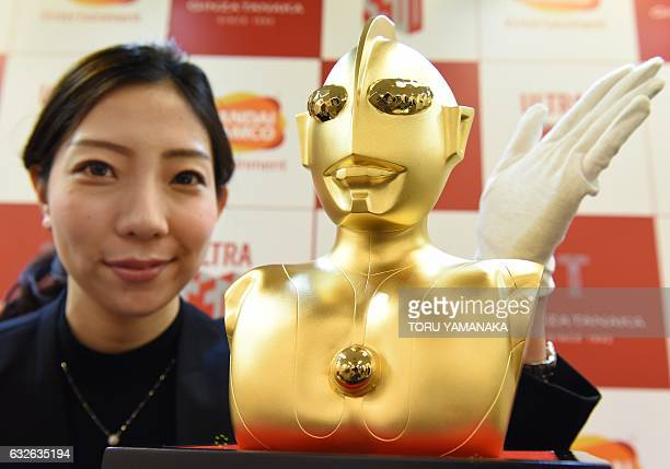 An employee of Japanese jeweler Ginza Tanaka poses with a pure gold bust of Japanese scifi hero Ultraman at the company's head office in Tokyo on...