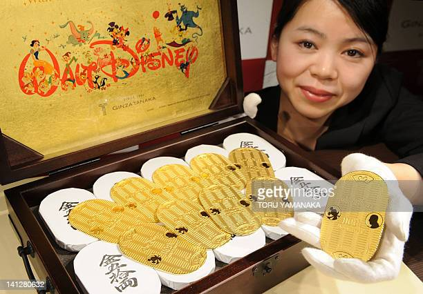 An employee of Japanese jeweler Ginza Tanaka shows off a special box filled with 50 pieces of 100g oval pure gold coins engraved with Walt Disney and...