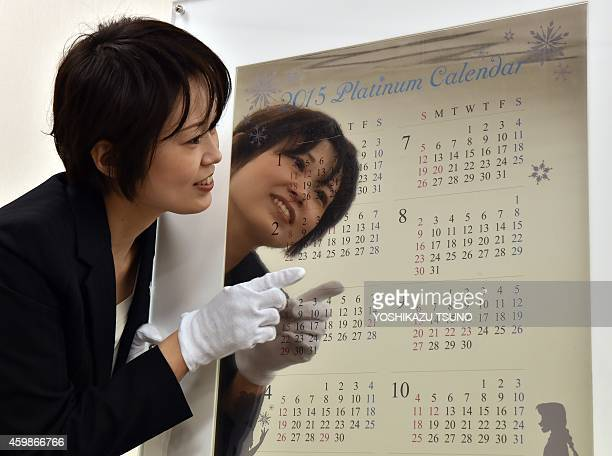 An employee of Japanese jeweler Tanaka Kikinzoku Jewelry displays a pure platinum made calendar for 2015 at the company's Ginza shop in Tokyo on...