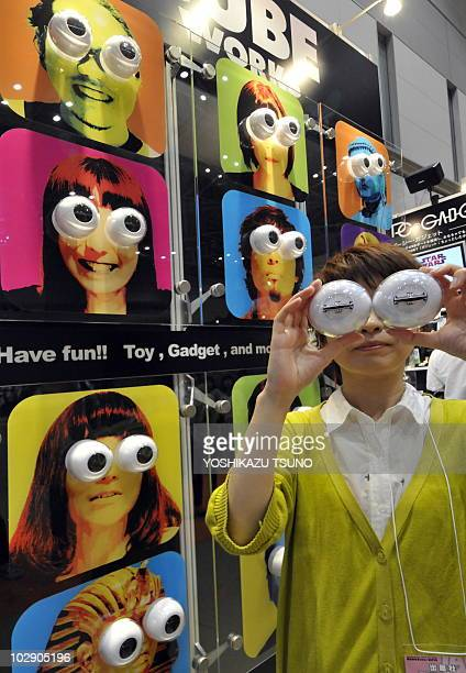 An employee of Japanese joke toy maker Cube displays a pair of large eyeballs 'Nikodama' at the annual Tokyo Toy Show in Tokyo on July 15 2010 Some...