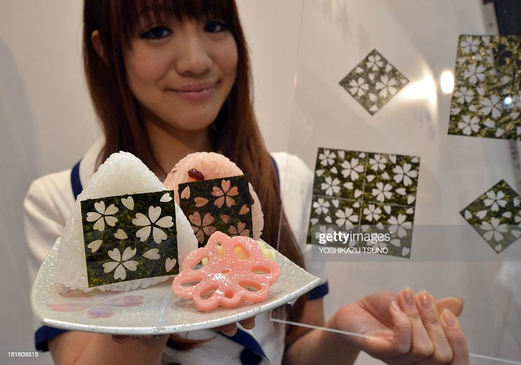 An employee of Japanese laver processing company Maruzen displays sheets of 'nori' or laver with cutting out patterns of cherry blossoms at the annual supermarket and trade show in Tokyo on February 13, 2013. The company made arts with laser processing on the sheets of Japanese popular food. AFP PHOTO / Yoshikazu TSUNO