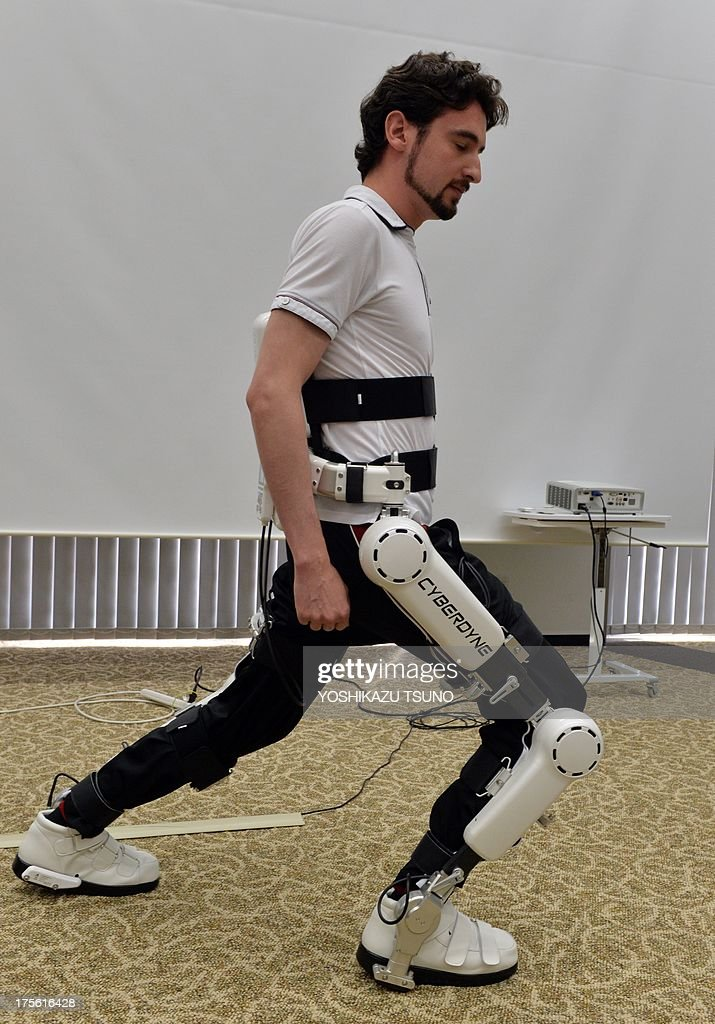 An employee of Japanese robot venture Cyberdyne demonstrates new robot suit Hybrid Assistive Limb (HAL) for medical use, developed by University of Tsukuba professor Yoshiyuki Sankai, at the Cyberdyne headquarters in Tsukuba, suburban Tokyo on August 5, 2013. The HAL, which is designed to learn the user's motion and assist their movement, can be used for the rehabilitation of disabled and assist elderly people, was authenticated as a medical device in Europe by European certification authority. AFP PHOTO / Yoshikazu TSUNO