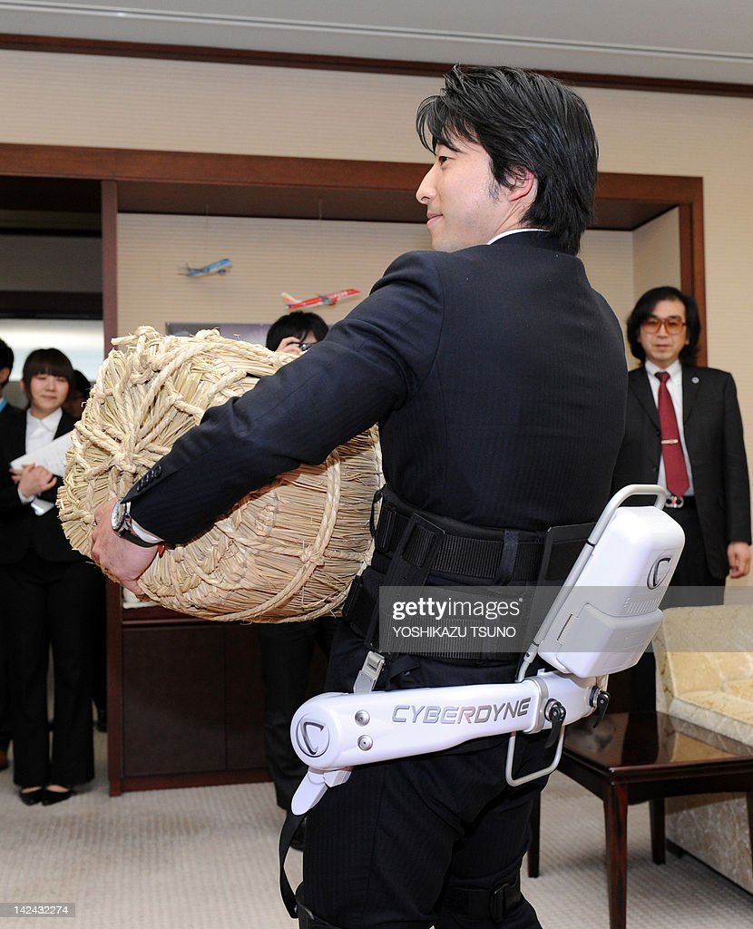 An employee of Japanese robotic venture Cyberdyne carries a 65 kilogram straw rice bag during a demonstration of the new robot suit 'HAL' (Hybrid Assistive Limb) to support user's when lifting heavy goods at the Niigata prefectural office in Niigata city, northern Japan on April 5, 2012. Tsukuba University professor and Cyberdyne President Yoshiyuki Sankai (R) developed two prototype models of the robot suits for nurses and care workers, and will start field tests at hospitals and nursing homes in Niigata from June. AFP PHOTO / Yoshikazu TSUNO