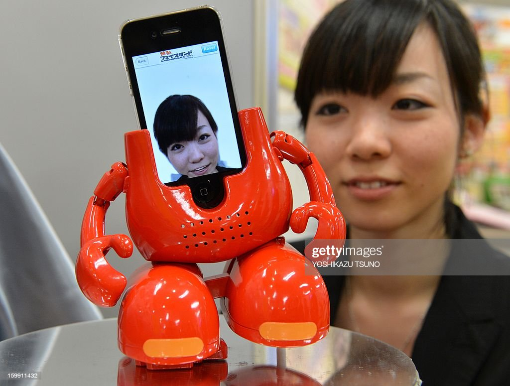 An employee of Japanese toy maker Tomy displays a new virtual dancing robot 'Dancing Face-stand for iPhone', which is used to dock iPhones on its face and react to the music stored in the iPhone at a press preview in Tokyo on January 23, 2013. The face morphing application is provided by software venture Motion Portrait at App Store. AFP PHOTO / Yoshikazu TSUNO