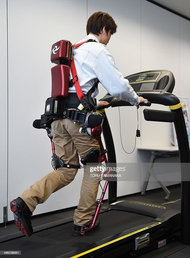 An employee of Japan's Activelink shows the company's power-assisted POWERLOADER light PLL-04 suit, called the 'Ninja', runs on a treadmill to show its capabilities at a demonstration in Tokyo on June 2, 2014. The suit will be tested to verify its purpose and effectiveness, mainly in the fields of forestry and agriculture, where work efficiency on slopes is required. AFP PHOTO / Toru YAMANAKA