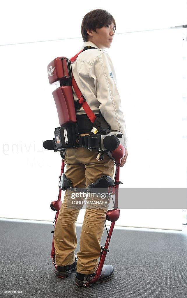 An employee of Japan's Activelink shows the company's power-assisted POWERLOADER light PLL-04 suit, called the 'Ninja', at a demonstration in Tokyo on June 2, 2014. The suit will be tested to verify its purpose and effectiveness, mainly in the fields of forestry and agriculture, where work efficiency on slopes is required. AFP PHOTO / Toru YAMANAKA