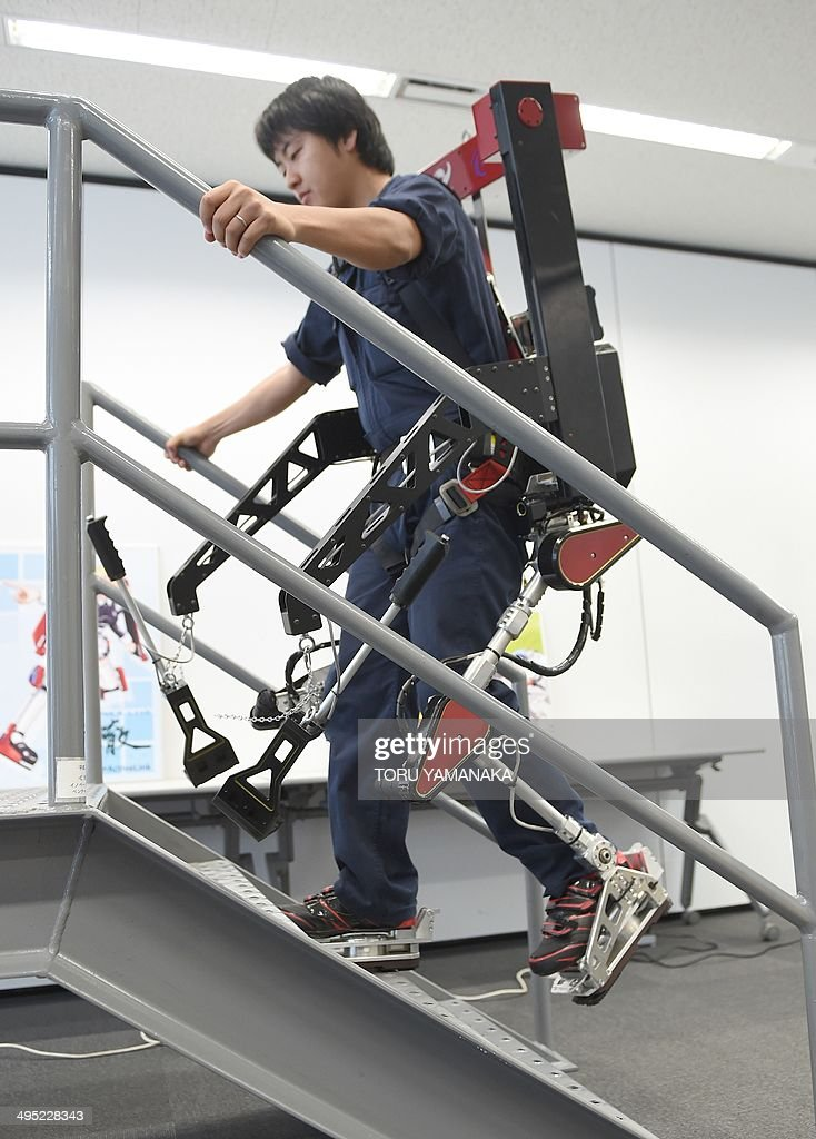 An employee of Japan's Activelink, wearing the company's power assisted POWERLOADER light PLL-01E suit, called 'Ittetsu', walks up stairs to display its capabilities at a demonstration in Tokyo on June 2, 2014. The company developed the elements to put the 45-kg powered suits into practical use for many industries, such as agriculture, construction, at nuclear plants, for defense, welfare and medical care. AFP PHOTO / Toru YAMANAKA