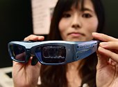 An employee of Japan's computer giant Fujitsu displays a prototype of the 'Retissa' retinal imaging eyewear which can project digital images onto the...