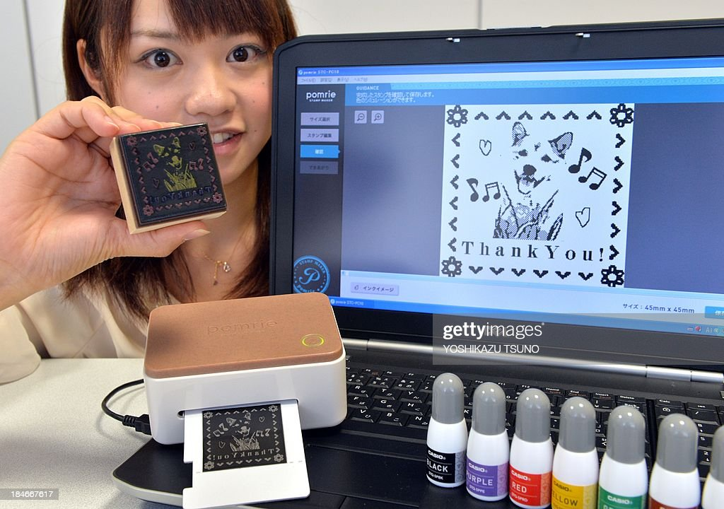 An employee of Japan's electronics maker Casio Computer displays a stamp maker 'Pomrie' which goes on sale on November 8, at the company's headquarters in Tokyo on October 11, 2013. Japan's Casio Computer has found a way to marry Japan's love of ink stamps with its technological wizardry in the form of a desk-top device. AFP PHOTO / Yoshikazu TSUNO