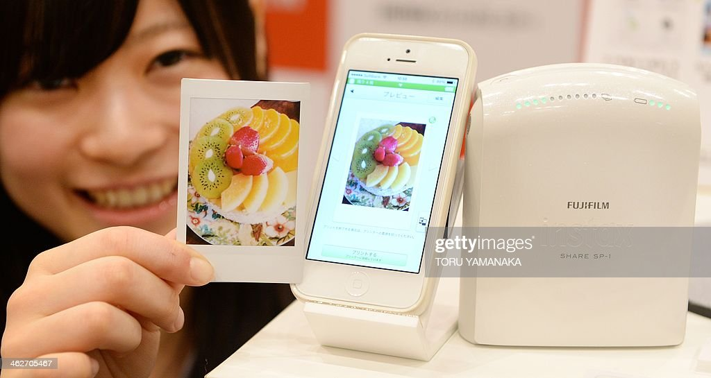 An employee of Japan's FUJI FILM introduces an instant smartphone printer, instax SHARE Smartphone Printer SP-1 (R), which creates from card-sized instant photo prints using images sent wirelessly from a smartphone during a press preview in Tokyo on January 15, 2014. The company will put the new product on the market on February 15 at an expected price of 190 USD. AFP PHOTO/Toru YAMANAKA