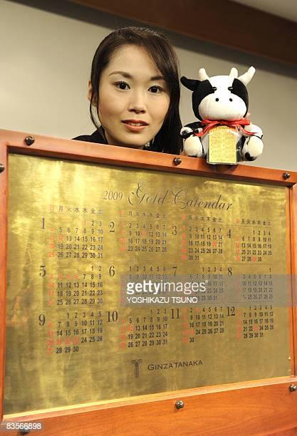 An employee of Japan's jeweler Tanaka Kikinzoku displays a ox mascot waering a 8 x 5cm gold foil calendar as she poses by a 2009 calendar made of...