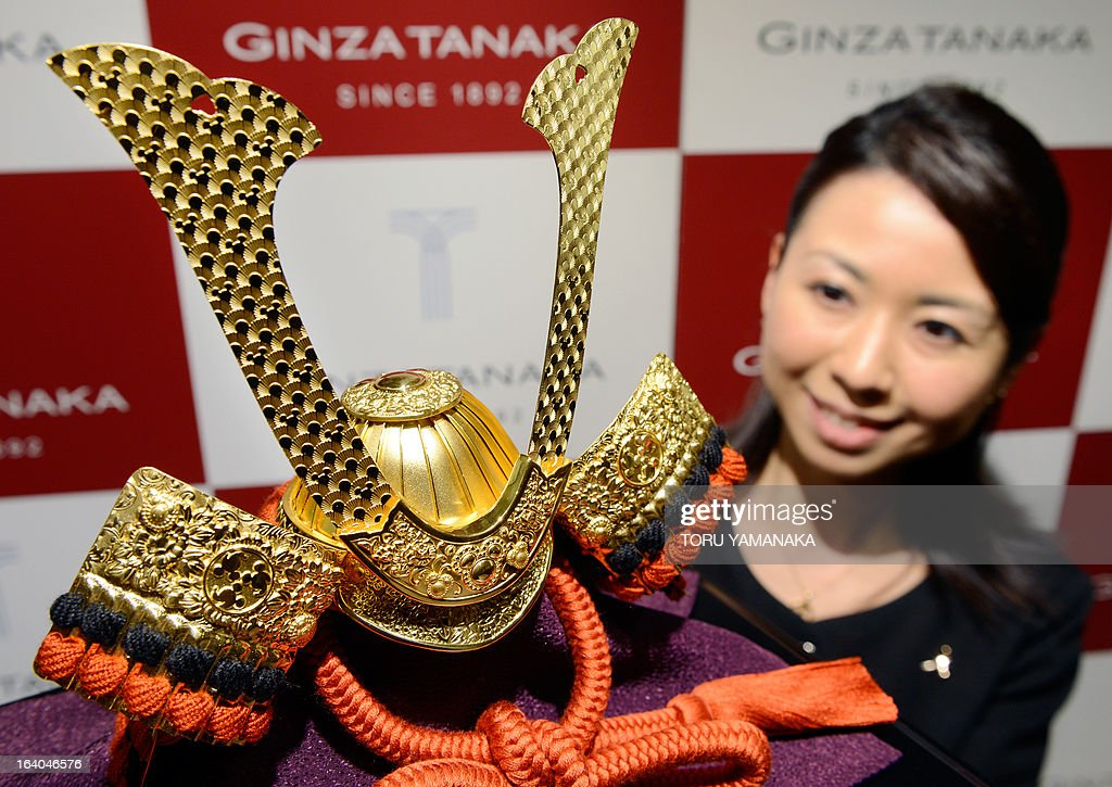 An employee of Japan's jeweler Tanaka Kikinzoku Jewelry displays a pure gold samurai helmet designed with Mickey Mouse logos at their main shop in Ginza shopping district in Tokyo on March 19, 2013. The Disney pure gold helmet will be on sale from March 20, ahead of Children's Day on May 5, a traditional festive event to celebrate the growth of children. AFP PHOTO / Toru YAMANAKA
