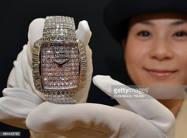 An employee of Japan's Mitsukoshi department store holds a 145 million USD jewelry wrist watch produced by Swiss jeweler Piaget for the annual world...