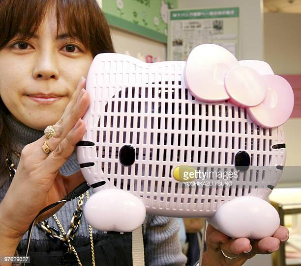 An employee of Japan's Sanrio displays the company's air purifier shaped as character Hello Kitty at the company's headquarters in Tokyo 05 March...