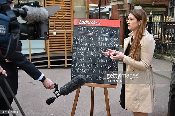An employee of Ladbrokes betting company is interviewed by a member of the media as she stands by a blackboard with the odds of the sex and name of...