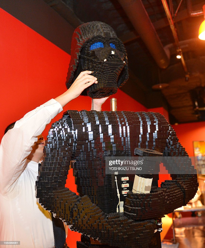 An employee of Lego Japan puts the head part of Darth Vader, a character of the US movie Star Wars in Tokyo on November 5, 2012 at the Legoland Discovery Center Tokyo. The characters of the Star Wars saga, set to be revived from 2015 under new owners Disney, will be displayed from November 6. AFP PHOTO / Yoshikazu TSUNO