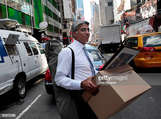 An employee of Lehman Brothers Holdings Inc carries a box out of the company's headquarters building September 15 2008 in New York City Lehman...