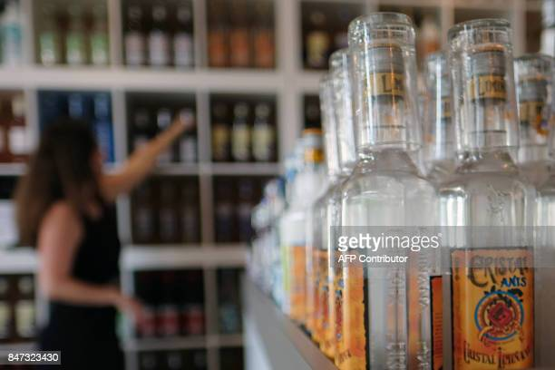 An employee of 'Liminana' company that manufactures Pastis arranges bottles at the company's shop in Marseille southern France on September 6 2017...