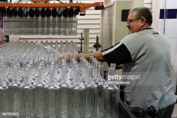 An employee of 'Liminana' company that manufactures Pastis controls bottles on an assembly line before filling at the company's plant in Marseille...