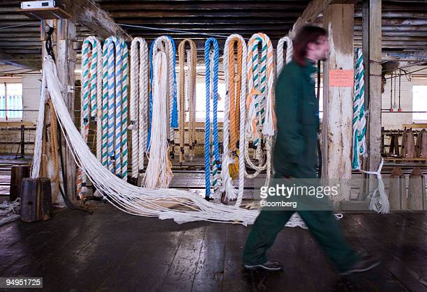 An employee of Master Ropemakers walks past a rack of ropes at their factory in Chatham dockyards Kent UK on Monday March 9 2009 UK manufacturing...