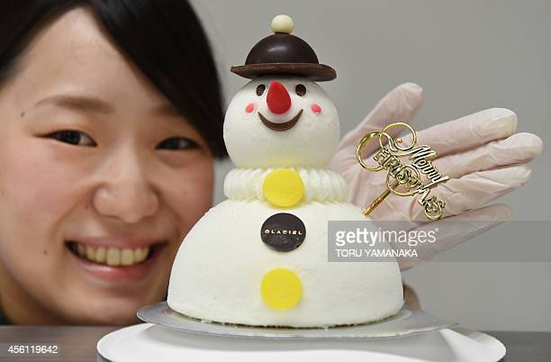 An employee of Mituskoshi Department Store introduces snowman ice cream cake for Christmas during a press preview in Tokyo on September 26 2014 The...