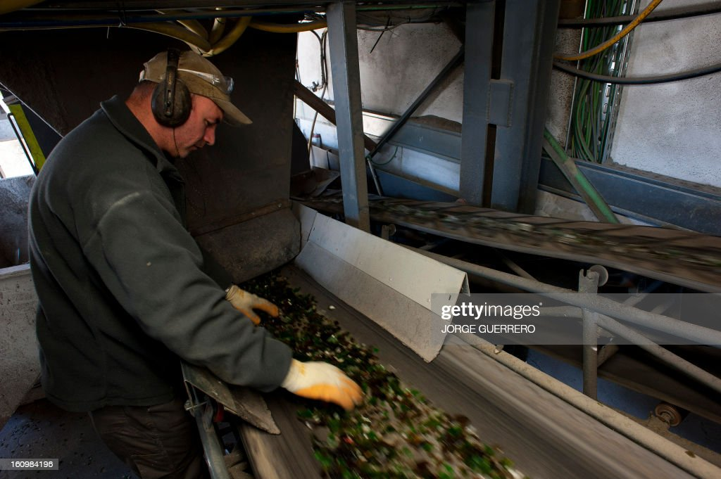 An employee of Movilsa separates plastic waste from pulverized glass waste at the Movilsa glass recycling center in Alhauri­n de la Torre, near Malaga, on February 8, 2013.