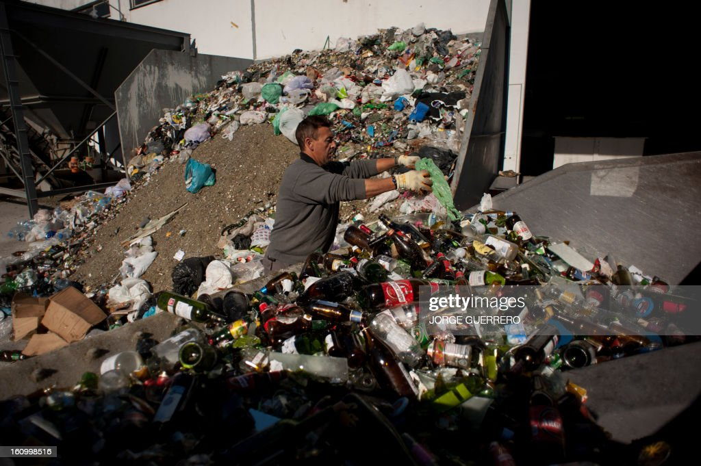 An employee of Movilsa separates plastic waste from used glass bottles at the Movilsa glass recycling center in Alhauri­n de la Torre, near Malaga, on February 8, 2013.