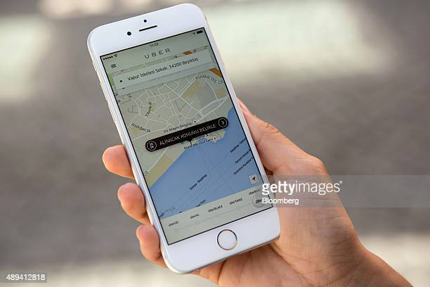 An employee of NavetteTezman Holding uses a smartphone to access the app used by the UberBOAT taxi service a unit of Uber Technologies Inc on the...