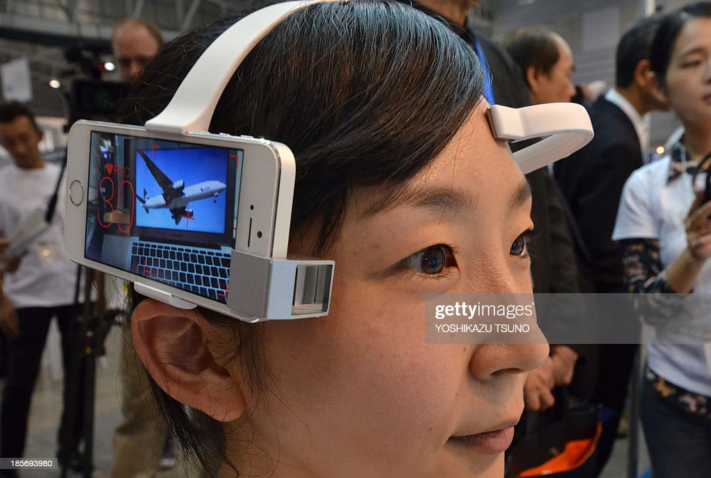 An employee of Neurowear wears a headset with a smartphone called 'Neurocam' at the Smart City Week exhibition in Yokohama, suburban Tokyo, on October 23, 2013. whThe devide can analyse the user's brain waves and video record scenes when it senses interest from the user. AFP PHOTO / Yoshikazu TSUNO