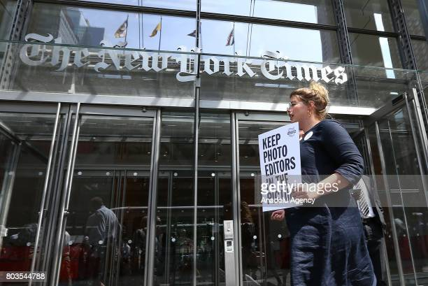An employee of New York Times holds a banner during a temporary strike against downsizing and dismissal plans of the NYT management outside of New...