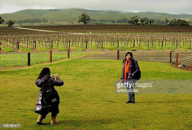 An employee of Pernod Ricard China distributors of Jacob's Creek Wines in China poses as a friend takes a photograph on July 20 2010 during a wine...