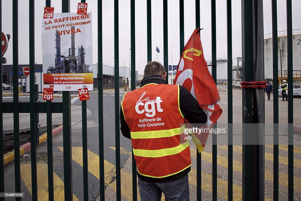 An employee of Petroplus oil refinery stands at the entrance of the 'Rubis' oil terminal on October 24, 2012 in Petit-Couronne, northwestern France. The court in Rouen ordered the liquidation of Petroplus on October 16, 2012, despite two offers for the site that employs 470 people. The court left open the possibility for other bidders to come forward by November 5 however, amid widespread anger among the refinery's workers.